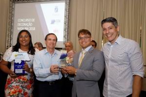 O presidente Romildo Barbosa da Silva Júnior e a executiva Ingrid da Silva de Assis recebendo o troféu das mãos do presidente da FCDL/RN, Afrânio Miranda.